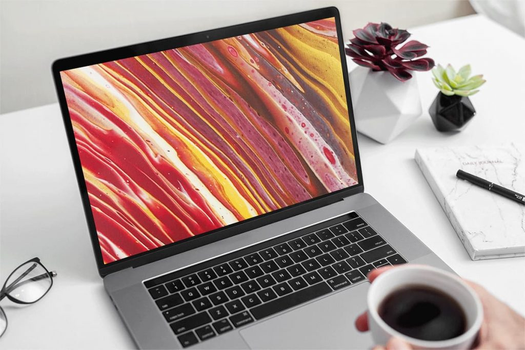 Open laptop with background of orange and red painting on it